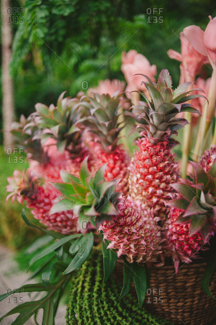 Decorative arrangement of red pineapples and tropical flowers