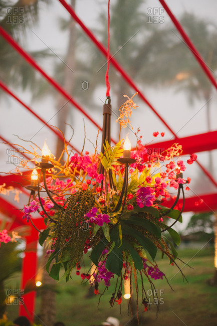 Hanging lamp with tropical flowers at wedding reception
