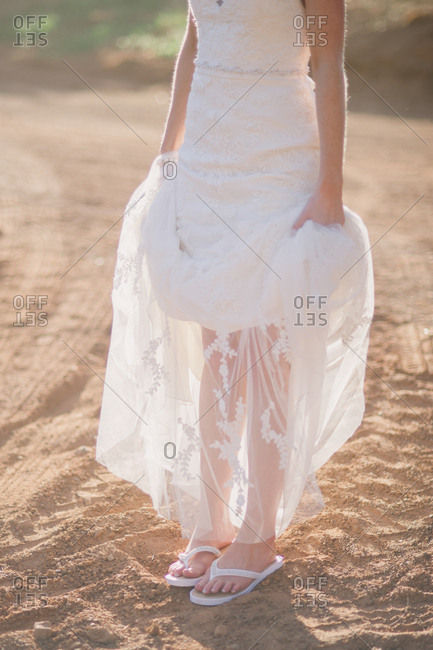 Bride standing on dirt road holding up sides of wedding dress