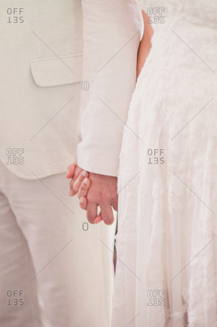 Close-up of bride and groom holding hands at wedding