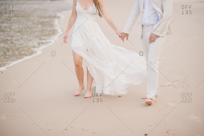 Bride and groom holding hands and walking barefoot on sandy beach