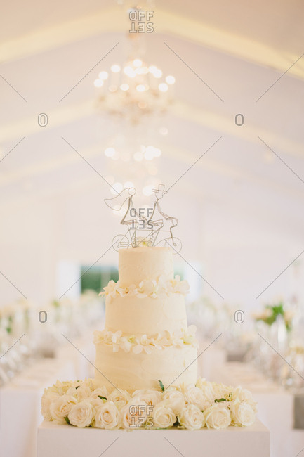 Wedding cake with white roses and bicycle cake topper