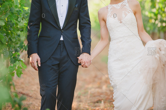Bride and groom holding hands while walking through vineyard