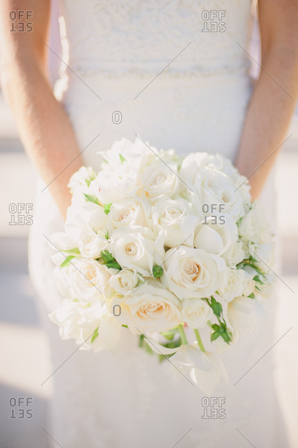Bride holding wedding bouquet of white roses