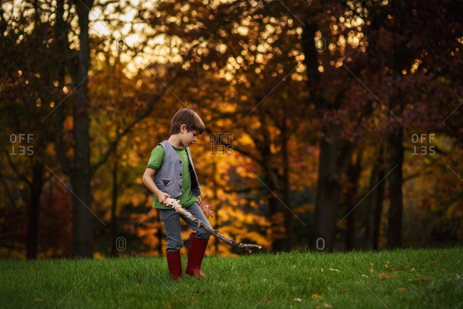 Young boy playing in the backyard in the fall