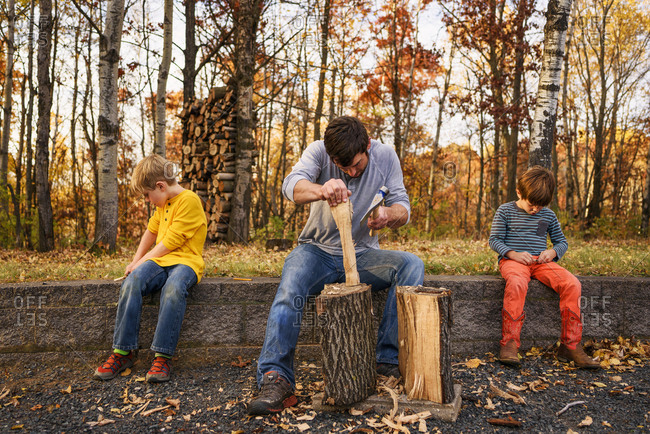 Man and two boys carving wood