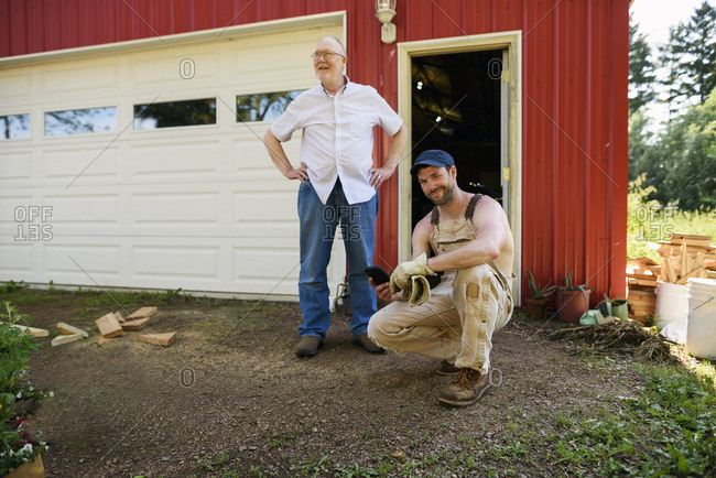 Two generations of men in front of a shed