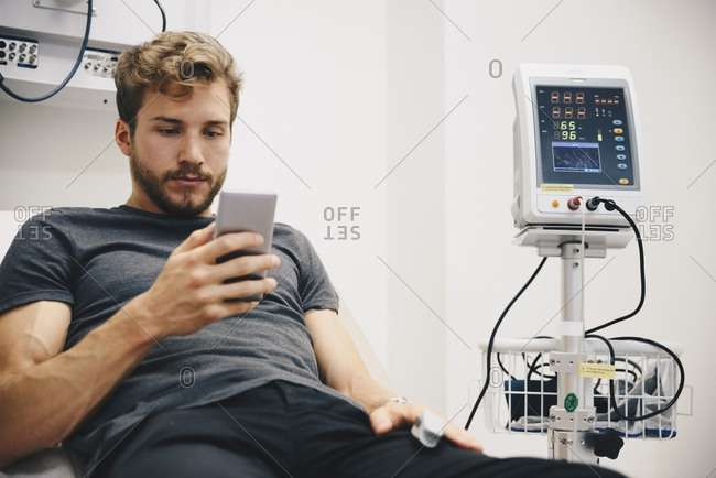 Young male patient using smart phone while reclining on bed during medical test in hospital