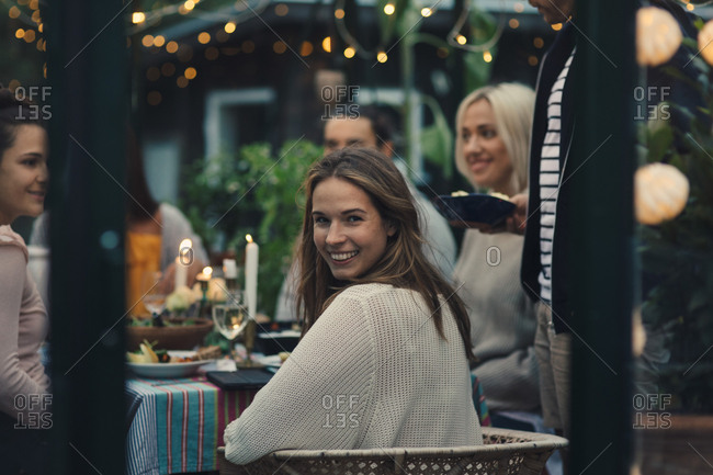 Smiling young woman looking back while sitting with friends in glass conservatory in back yard