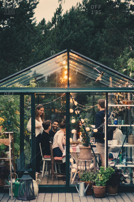 Happy young multi-ethnic group enjoying dinner party in conservatory at back yard