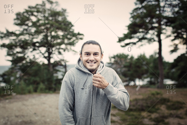 Portrait of smiling young man zipping hooded sweatshirt in back yard