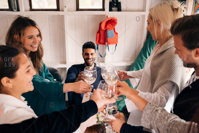 High angle view of happy young friends toasting wineglasses during lunch party