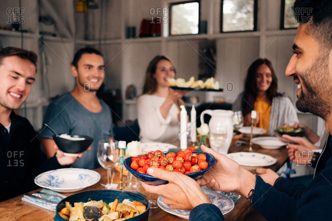 Young man holding bowl of strawberries while sitting with friends for lunch party