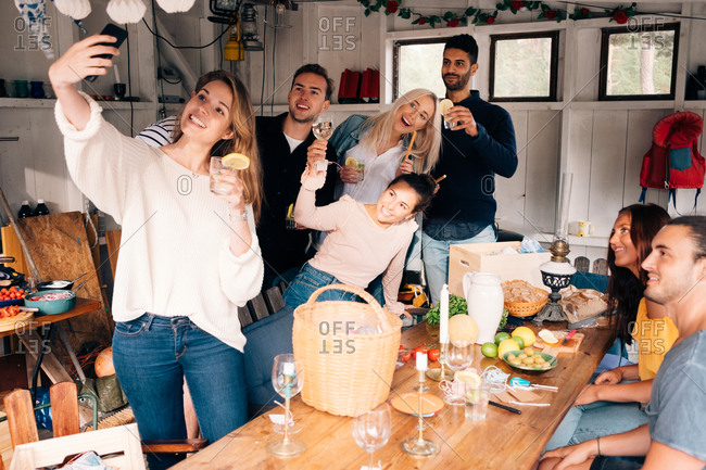Young woman taking selfie with friends during lunch party