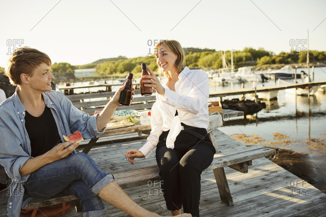Smiling male and female friends toasting beer bottles at harbor