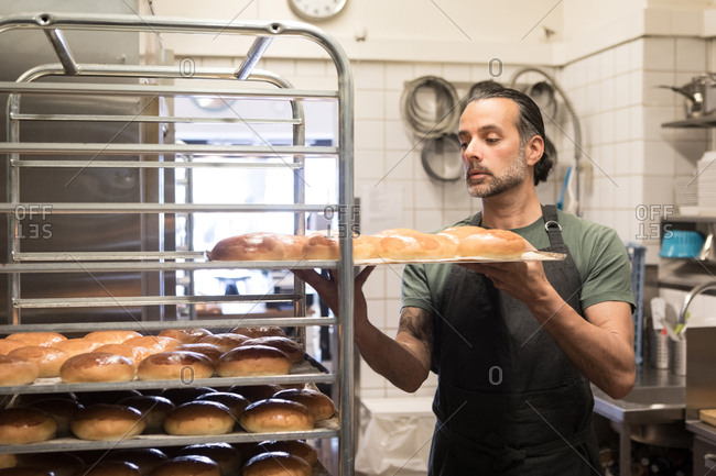 Confident mature male owner holding baking sheet with freshly baked breads on rack at bakery kitchen