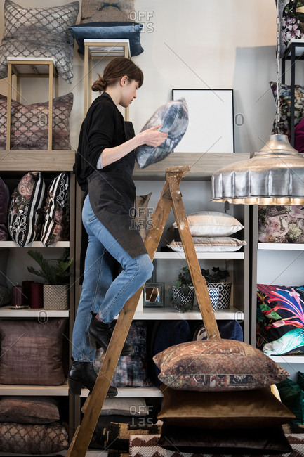 Full length of young female entrepreneur standing on ladder while arranging cushion in rack at store