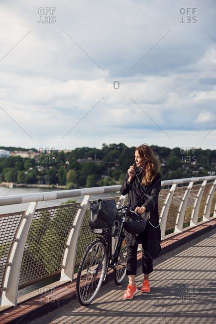 Mature woman talking through headphones while walking with bicycle on footbridge against sky