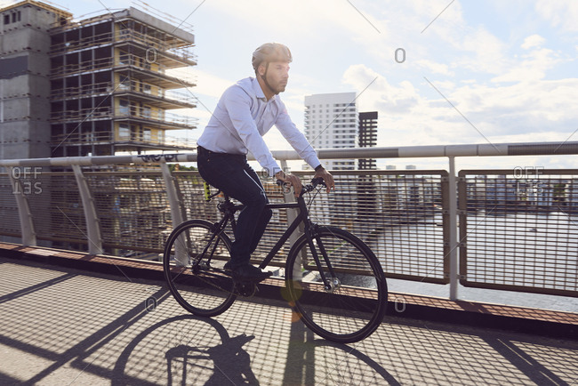 Businessman cycling on footbridge against sky