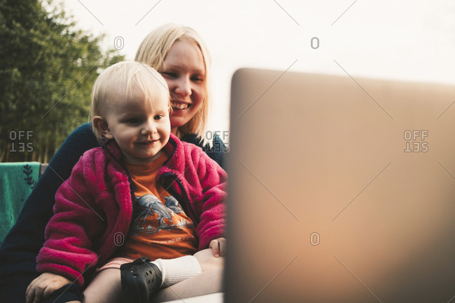 Smiling mother and daughter looking at laptop during video conference on sunny day