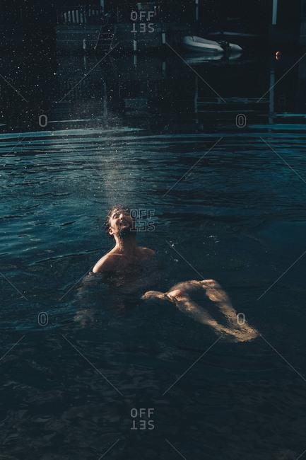 Full length of shirtless man diving in lake at holiday villa