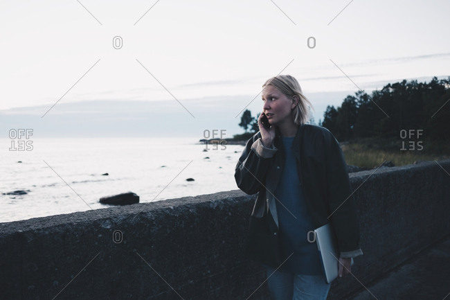 Woman talking on mobile phone and holding laptop while walking by lake against sky