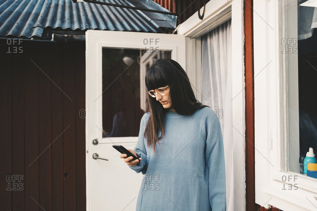 Woman using smart phone while standing outside holiday villa