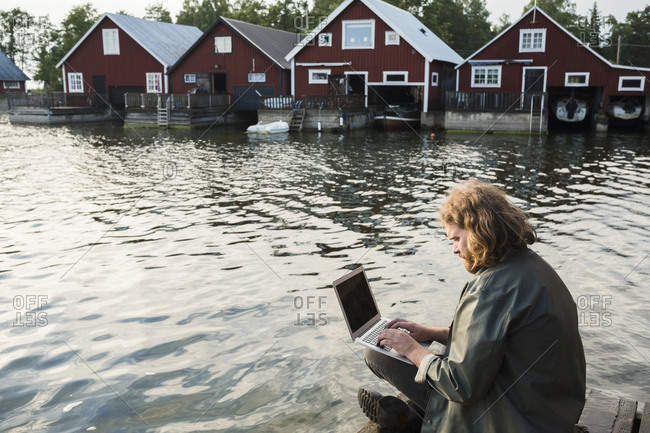Man using laptop while sitting on jetty by lake against holiday villas