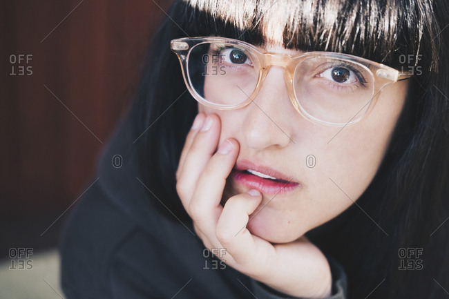 Portrait of woman wearing eyeglasses resting with hand on chin