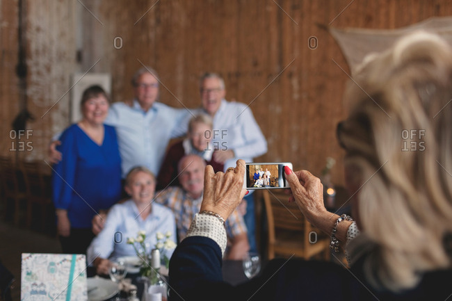 Senior woman photographing happy friends sitting at table in restaurant