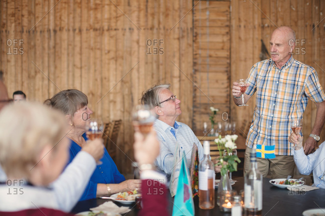 Senior man toasting drink to friends at table in restaurant