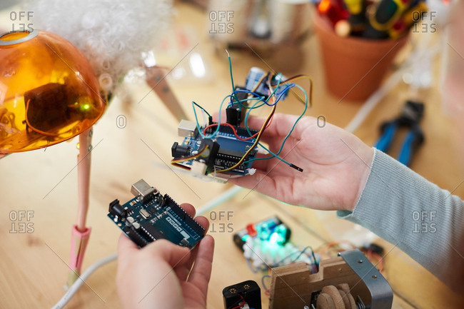 Cropped hands of young female technician holding electrical equipment at table in workshop