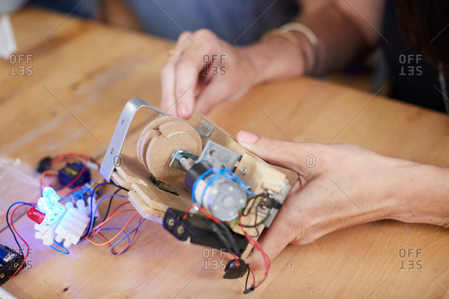 Cropped hands of mature female inventor making model at workshop