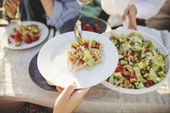 Close-up of woman serving pasta to friend at picnic table