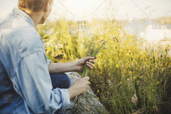 Side view of young man holding at flowers by plants