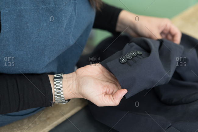 Midsection of female cleaner checking suit's sleeve at Laundromat