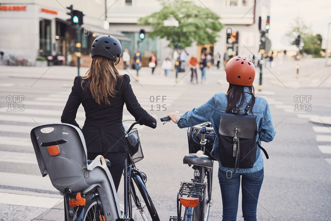 Rear view of females with bicycles crossing street in city