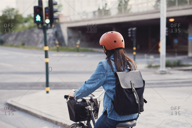Rear view of woman cycling on street