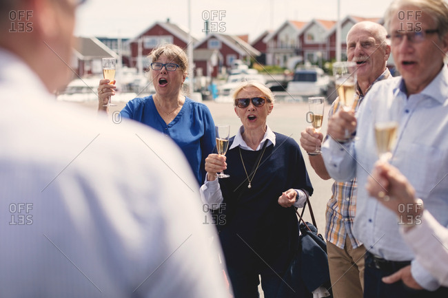 Male and female friends cheering while toasting champagne flutes outdoors