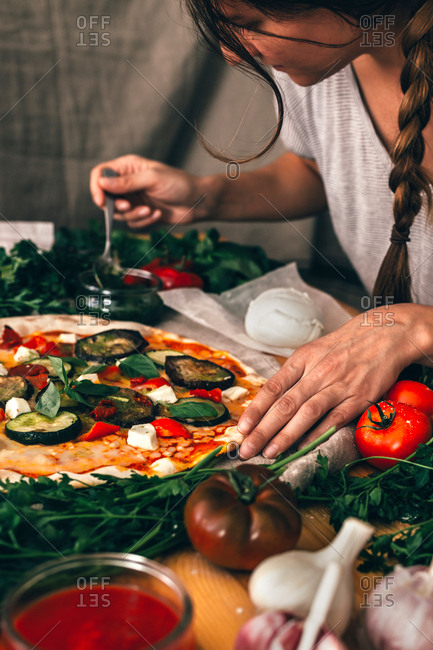 Casual woman pouring pizza with delicious sauce while cooking.