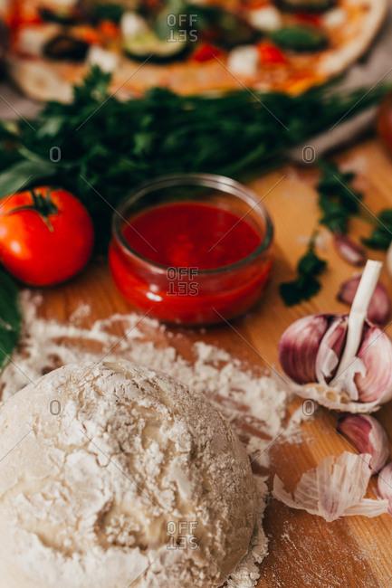 Kneaded dough in floor lying on wood in arrangement with cooking ingredients.