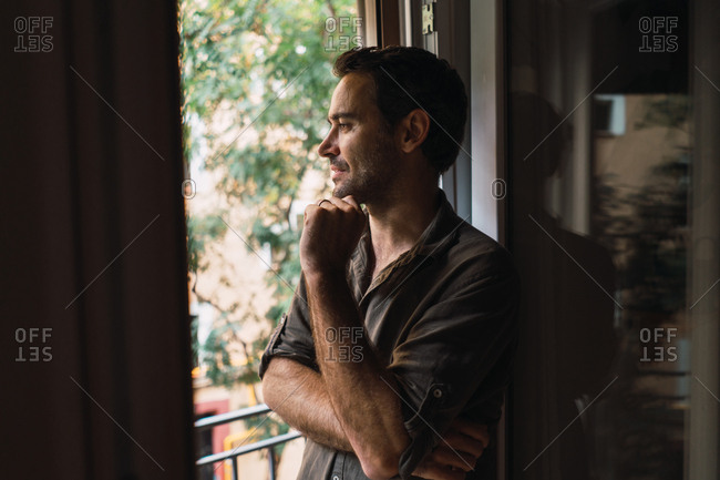 Pensive content man looking out of window