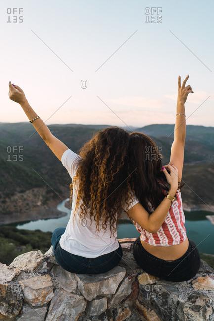 Stylish women sitting on rock in breathtaking landscape