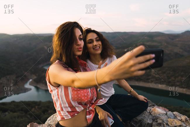 Stylish women taking selfie on breathtaking landscape