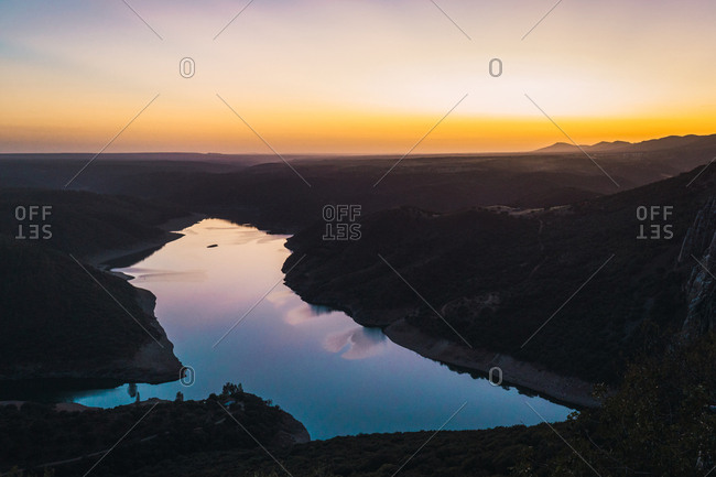 Amazing panorama of calm river reflecting colorful sunset sky while flowing in mountains.