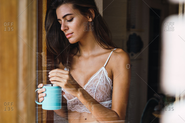 Woman in bra drinking coffee