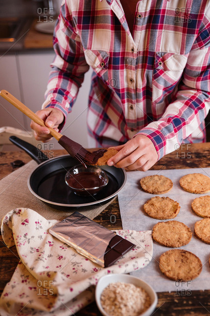 anonymous chef decorating cookies with melted chocolate using a silicone brush