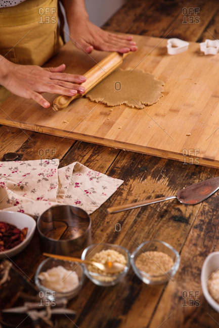 anonymous woman making homemade christmas cookies at home, kneading the dough