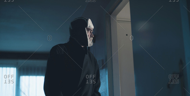 Man in woolen cap intruding dark living room.
