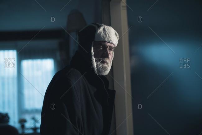 Intruder in woolen cap standing in living room.